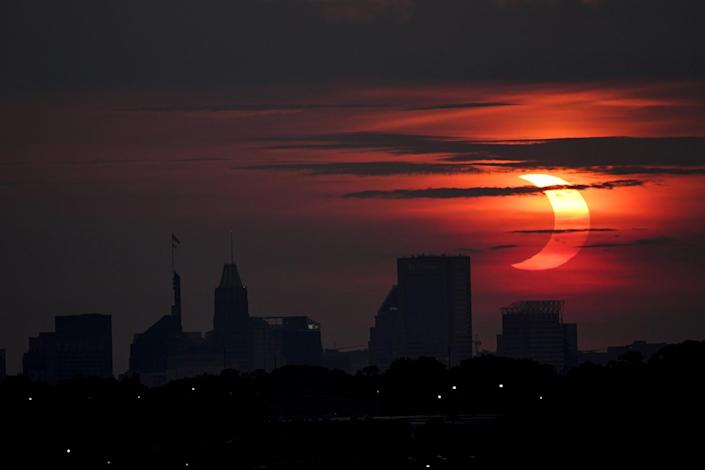 A partial solar eclipse rises over the Baltimore skyline, as seen from Arbutus, Md.