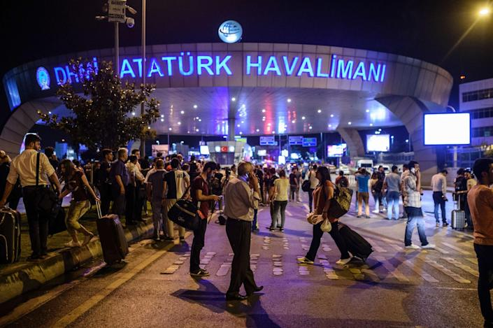 <p>People stand outside the entrance as they leave the airport after two explosions followed by gunfire hit the Turkey's biggest airport of Ataturk in Istanbul, on June 28, 2016. (OZAN KOSE/AFP/Getty Images) </p>