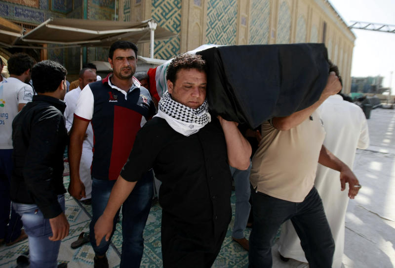 Mourners carry the coffin of a car bomb victim during his funeral in the Shiite holy city of Najaf, 100 miles (160 kilometers) south of Baghdad, Iraq, Sunday, Sept. 22, 2013. Two suicide bombers, one in an explosives-laden car and the other on foot, hit a cluster of funeral tents packed with mourning families in a Shiite neighborhood in Baghdad, the deadliest in a string of attacks around Iraq that killed scores on Saturday. (AP Photo)