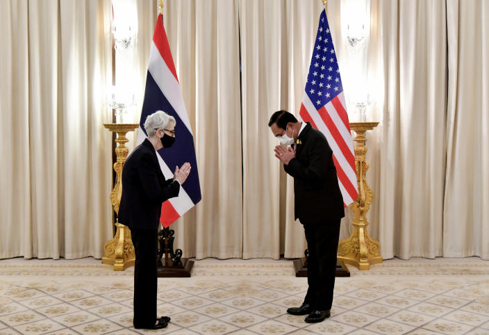 """In this photo released by Government Spokesman Office, U.S. Deputy Secretary of State Wendy R. Sherman, left, and Thailand's Prime Minister Prayuth Chan-ocha, right, give the traditional greeting or """"wai"""" at Government House in Bangkok, Thailand, Wednesday, June 2, 2021. (Government Spokesman Office via AP)"""