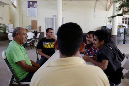 Mexican deportees talk to a volunteer at Our Lady of Guadalupe migrant shelter in Reynosa