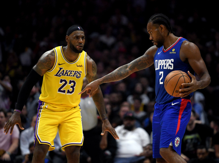 Kawhi Leonard of the Clippers controls the ball in front of Lakers forward LeBron James.