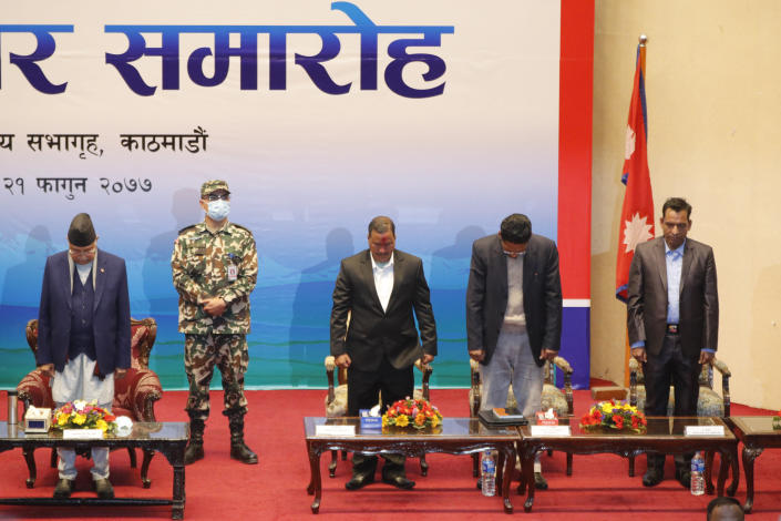 Nepalese Prime Minister Khadga Prassad Oli, left, and leader of Nepal Communist Party group Netra Bikram Chand, third right, along with others pay respects to martyrs during a signing of peace agreement in Kathmandu, Nepal, Friday, March 5, 2021. Chand, who is better known by his guerrilla name Biplav, emerged out of hiding on Friday after the government lifted a ban on his group so it could take part in the public signing of the peace agreement. This group had split from the Maoist Communist party, which fought government troops between 1996 and 2006, when it gave up its armed revolt, agreed to U.N.-monitored peace talks and joined mainstream politics. (AP Photo/Niranjan Shrestha)
