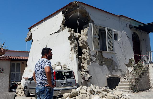 <p>A person stands in front of a damaged house after an earthquake hits the island of Ischia, off the coast of Naples, Italy, Aug. 22, 2017. (Photo: Ciro De Luca/Reuters) </p>