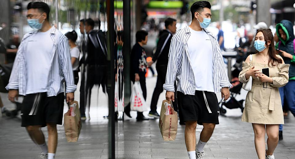 A man and a woman are seen walking down a Sydney street wearing face masks. Source: AAP