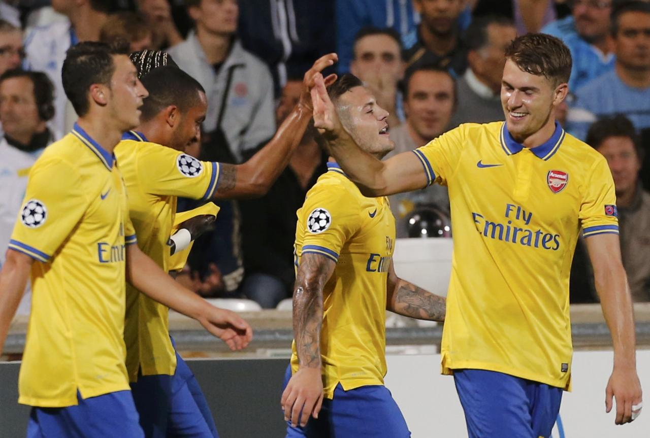 Arsenal Players celebrate after Theo Walcott scored against Olympique Marseille during their Group F Champions League soccer match at the Velodrome stadium in Marseille, September 18, 2013. REUTERS/Jean-Paul Pelissier (FRANCE - Tags: SPORT SOCCER)