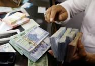FILE PHOTO: A man counts Lebanese pounds at a currency exchange shop in Beirut