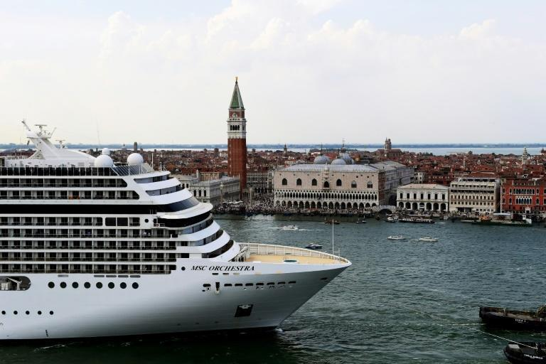 Tugboats escort the MSC Orchestra cruise ship across the basin past the Bell Tower and the Doge's palace