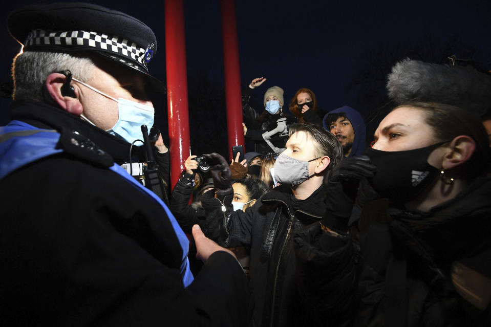 People react with police, in Clapham Common as people gather, despite the Reclaim These Streets vigil for Sarah Everard being officially cancelled, in London, Saturday, March 13, 2021. A serving British police officer accused of the kidnap and murder of a woman in London has appeared in court for the first time. Wayne Couzens, 48, is charged with kidnapping and killing 33-year-old Sarah Everard, who went missing while walking home from a friend's apartment in south London on March 3. (Victoria Jones/PA via AP)