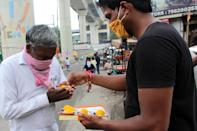 People distribute Laddoo's (sphere-shaped sweet) in New Delhi as Prime Minister Narendra Modi participated in a ''Bhoomi Pujan'' or a groundbreaking ceremony to mark the building of a grand Ram temple at Ayodhya in Uttar Pradesh, on August 5, 2020. The Ayodhya dispute came to a conclusion last year with the ruling of Supreme Court when it asked the Union government to handover the site for the construction of Ram temple. (Photo by Mayank Makhija/NurPhoto via Getty Images)