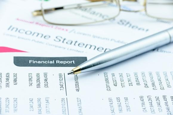 An income statement with a pen and glasses on top of it.