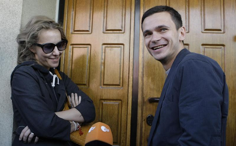 Russian opposition activist and television host Kseniya Sobchak, daughter of the late St. Petersburg mayor Anatoly Sobchak, left, and opposition leader Ilya Yashin, right, smile as they speak to the press at the headquarter of the Russian Investigation committee in Moscow, Russia, Tuesday June 12, 2012. Russia's top investigation agency has summoned several key opposition figures for questioning in an apparent bid to disrupt the first massive protest against President Vladimir Putin since his inauguration for a third term. (AP Photo/Mikhail Metzel)