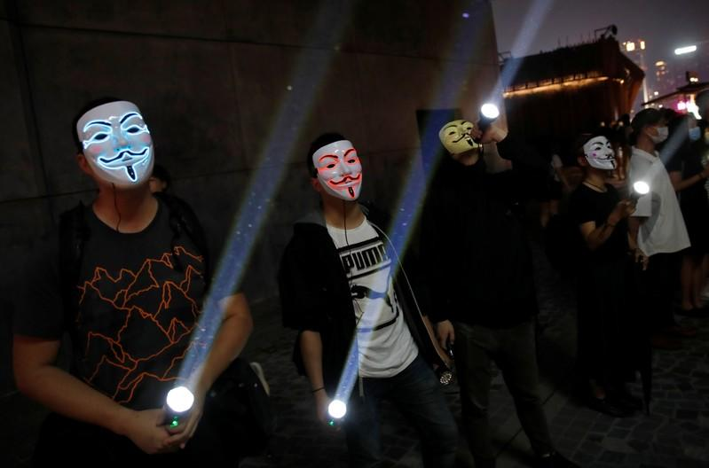 People wearing Anonymous masks use flashlights during an anti-government protest in Hong Kong