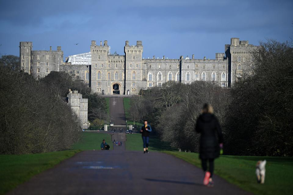 A woman walks with a dog along the Long Walk at Windsor Castle in Windsor, west of London on January 9, 2020. - Britain's Prince Harry and his wife Meghan stunned the British monarchy on Wednesday by quitting as front-line members -- reportedly without first consulting Queen Elizabeth II. In a shock announcement, the couple said they would spend time in North America and rip up long-established relations with the press. Media reports said the Duke and Duchess of Sussex made their bombshell statement without notifying either Harry's grandmother the monarch, or his father Prince Charles. (Photo by DANIEL LEAL-OLIVAS / AFP) (Photo by DANIEL LEAL-OLIVAS/AFP via Getty Images)