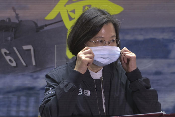"""In this image from a video, Taiwanese President Tsai Ing-wen adjusts her face mask while delivering a speech to the servicemembers of the 131st Flotilla in the northern port of Keelung, Taiwan Monday, March 8, 2021. Tsai visited a naval base on Monday to thank sailors and marines for their dedication to protecting the island amid renewed threats from China, vowing not to allow the loss of """"any single inch"""" of territory. (AP Photo/Johnson Lai)"""