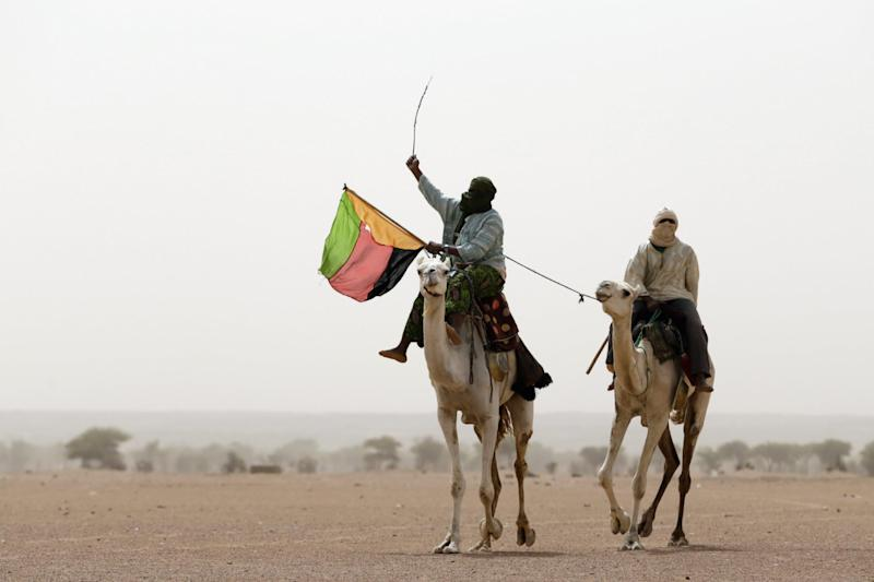 A Tuareg man holds the flag of the National Movement for the Liberation of Azawad (MLNA) during a demonstration on July 28, 2013 in Kidal
