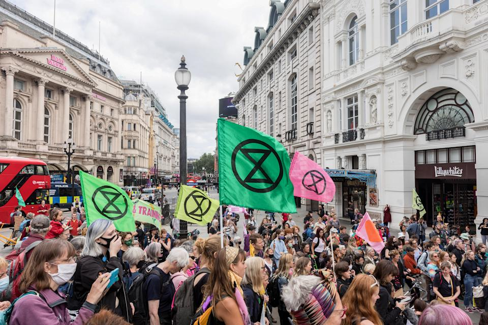 LONDON, UNITED KINGDOM - 2021/08/25: Protesters hold XR flags during the demonstration. On the 3rd day of Extinction Rebellion's protests, protesters came together with the aim of demanding climate justice for the Indigenous people of Amazon rainforests in Brazil. They protest against ecocide and deforestation in Brazil. The group began their demonstration outside Brazilian Embassy in London, then moved over to Piccadilly Circus, and lastly occupying Oxford Circus. (Photo by Belinda Jiao/SOPA Images/LightRocket via Getty Images)
