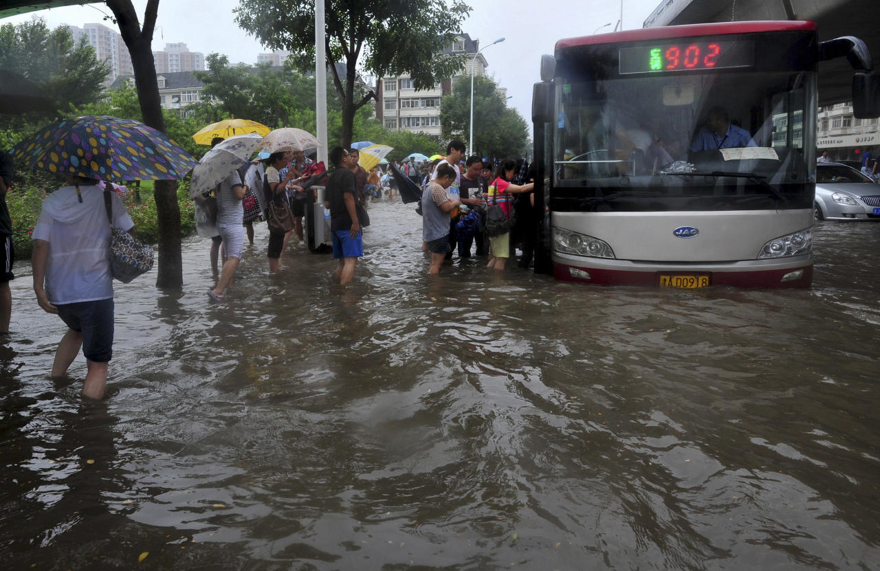 Commuters try to get on a bus on a flooded road following a heavy rain, in Tianjin, China Thursday, July 26, 2012. Residents impatient for official updates compiled their own death tolls Thursday for last weekend's massive flooding in Beijing and snapped up survival gear following new forecasts of rain, reflecting deep mistrust of the government's handling of the disaster. (AP Photo) CHINA OUT