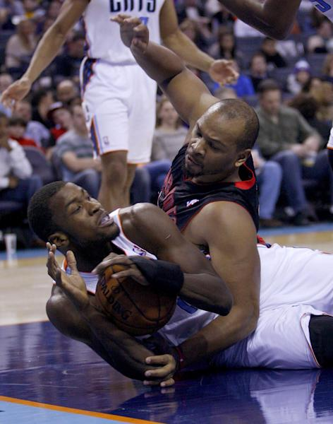 CORRECTS DATE - Charlotte Bobcats forward Michael Kidd-Gilchrist, left, and Toronto Raptors forward Chuck Hayes battle for a loose ball in the first half of an NBA basketball game Monday, Jan. 20, 2014 in Charlotte, N.C. (AP Photo/Nell Redmond)