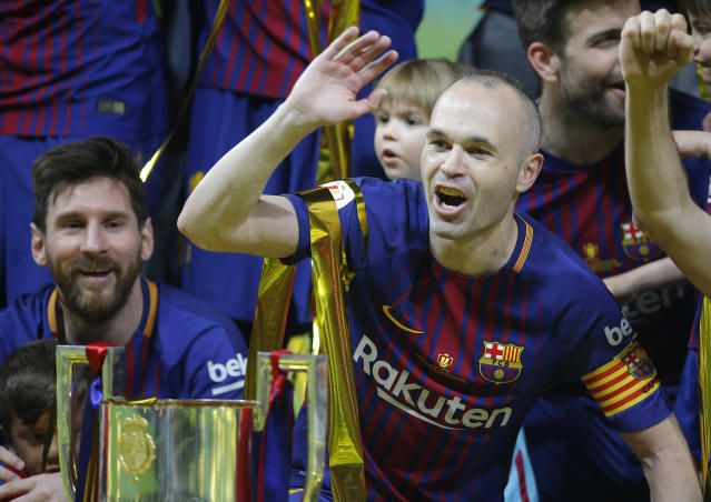 FC Barcelona's Andres Iniesta, right, and Lionel Messi celebrate during an award ceremony after defeating Sevilla 5-0 in the Copa del Rey final soccer match at the Wanda Metropolitano stadium in Madrid, Spain, Saturday, April 21, 2018. (AP Photo/Paul White)