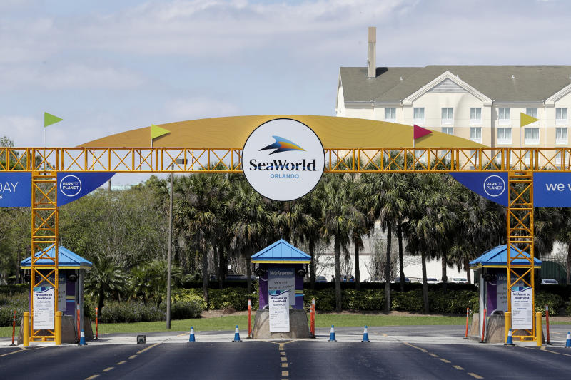 The entrance to the SeaWorld Theme park remains closed Monday, March 30, 2020, in Orlando, Fla. SeaWorld is indefinitely furloughing more than 90% of its employees and they won't get paid after March 31. (AP Photo/John Raoux)
