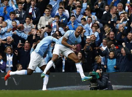 Manchester City's captain Vincent Kompany (R) celebrates after scoring against West Ham United during their English Premier League soccer match at the Etihad Stadium in Manchester, northern England May 11, 2014. REUTERS/Darren Staples