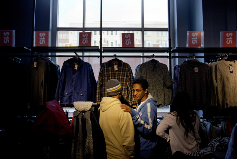 In this Wednesday, Dec. 12, 2012, photo, Chris Ghiathi, right, shops with friend Shawn Patel, left, in an H&M store, in Atlanta. U. S. consumers increased their spending in December at a slower pace, while their income grew by the largest amount in eight years. Income surged because companies rushed to pay dividends before income taxes increased on high-earners. (AP Photo/David Goldman)