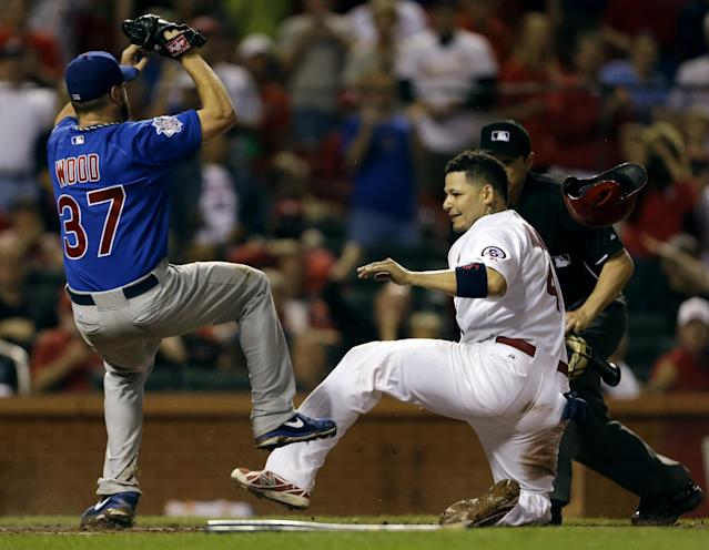 St. Louis Cardinals' Yadier Molina, right, is safe at home after being tagged late by Chicago Cubs starting pitcher Travis Wood during the seventh inning of a baseball game on Monday, June 17, 2013, in St. Louis. Molina scored on a throwing error by Cubs first baseman Anthony Rizzo. (AP Photo/Jeff Roberson)