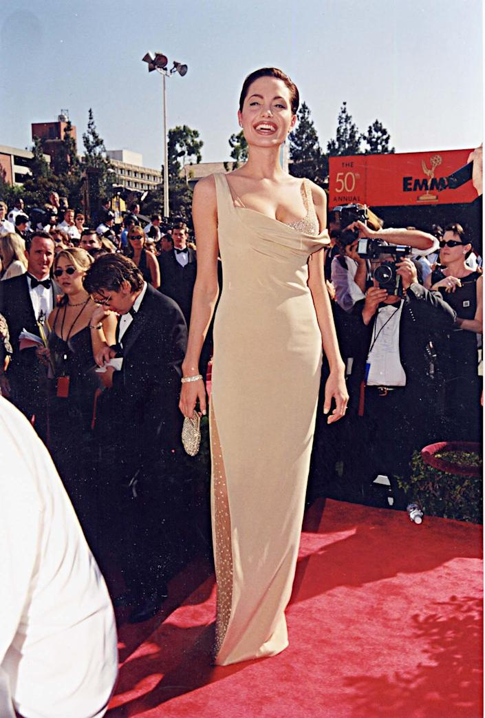 Angelina Jolie at the 1998 Emmys wearing a nude color gown on the red carpet