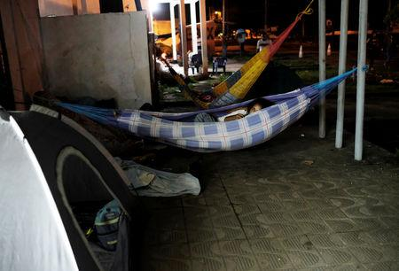 FILE PHOTO: Venezuelan people rest in hammocks along the street as they wait to show their passports or identity cards next day at the Pacaraima border control, Roraima state, Brazil August 9, 2018. Picture taken August 9, 2018. REUTERS/Nacho Doce