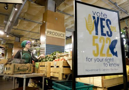 An employee stocks produce near a sign supporting a ballot initiative in Washington state that would require labeling of foods containing genetically modified crops at the Central Co-op in Seattle, Washington in this file photo taken October 29, 2013.  REUTERS/Jason Redmond/Files