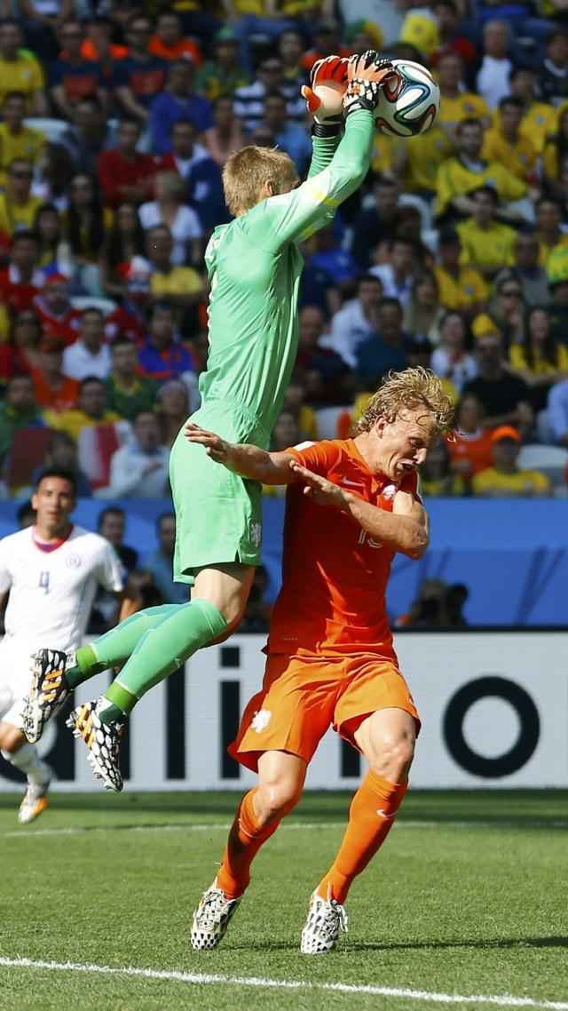 Goalkeeper Jasper Cillessen of the Netherlands (L) makes a save next to teammate Dirk Kuyt during their 2014 World Cup Group B soccer match against Chile at the Corinthians arena in Sao Paulo June 23, 2014. REUTERS/Ivan Alvarado (BRAZIL - Tags: SOCCER SPORT WORLD CUP)