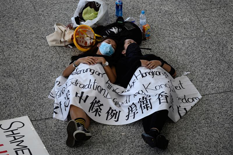 Protesters rest on the floor of Hong Kong's international airport on August 13, 2019, the day after the airport closed due to pro-democracy protests. (Photo: Philip Fong/NurPhoto via Getty Images)