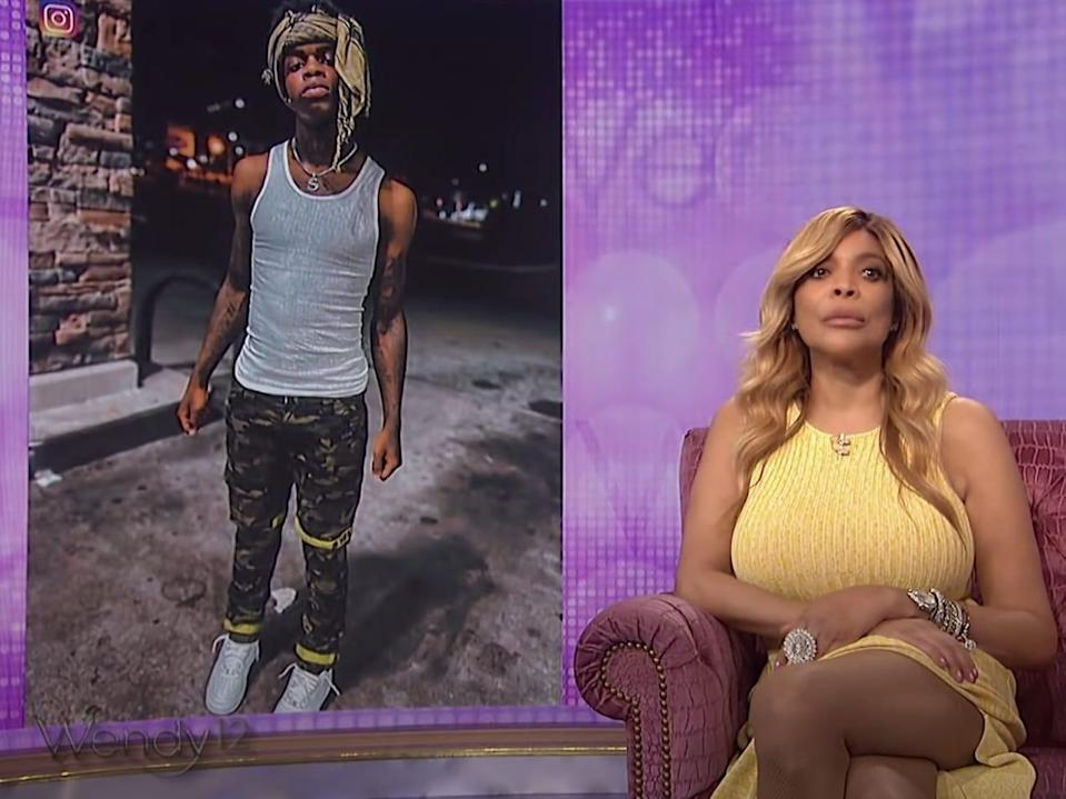 wendy williams sitting in a chair with a neutral expression on her face; behind her and to her left is a screen displaying an image of deceased tiktoker swavy