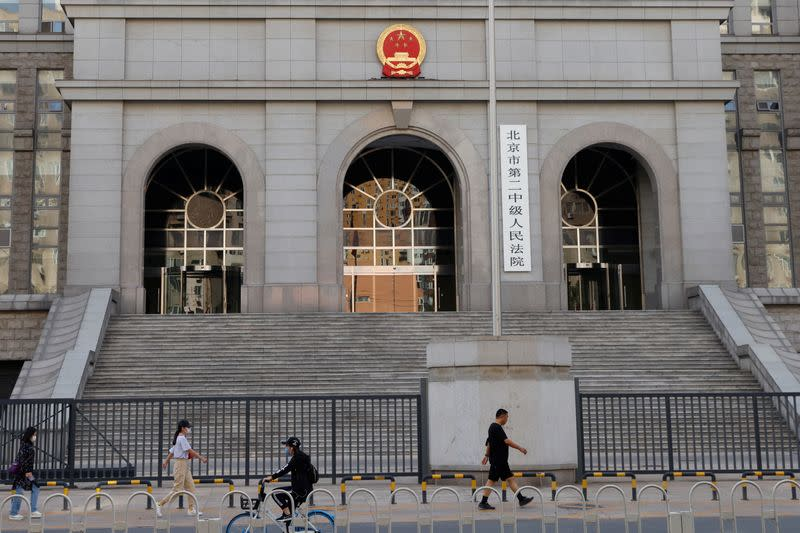 People walk past one of the entrances of Beijing No. 2 Intermediate People's Court where Australian writer Yang Hengjun is expected to face trial on espionage charges, in Beijing