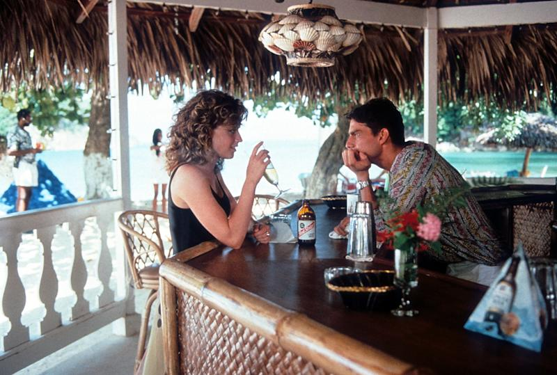 Elisabeth Shue visits Tom Cruise as he bartends in a scene from the film 'Cocktail', 1988. (Photo by Touchstone Pictures/Getty Images)
