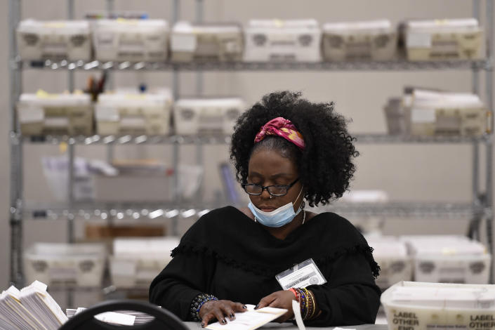 Cobb County Election officials handle ballots during an audit, Monday, Nov. 16, 2020, in Marietta, Ga. A hand tally of the nearly 5 million votes cast in the presidential race in Georgia has entered its fourth day Monday. (AP Photo/Mike Stewart)