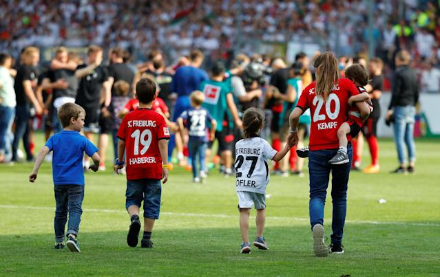 Soccer Football - Bundesliga - SC Freiburg v FC Augsburg - Schwarzwald-Stadion, Freiburg, Germany - May 12, 2018 Family members of SC Freiburg players celebrate on the pitch after the match after staying in the Bundesliga REUTERS/Kai Pfaffenbach DFL RULES TO LIMIT THE ONLINE USAGE DURING MATCH TIME TO 15 PICTURES PER GAME. IMAGE SEQUENCES TO SIMULATE VIDEO IS NOT ALLOWED AT ANY TIME. FOR FURTHER QUERIES PLEASE CONTACT DFL DIRECTLY AT + 49 69 650050