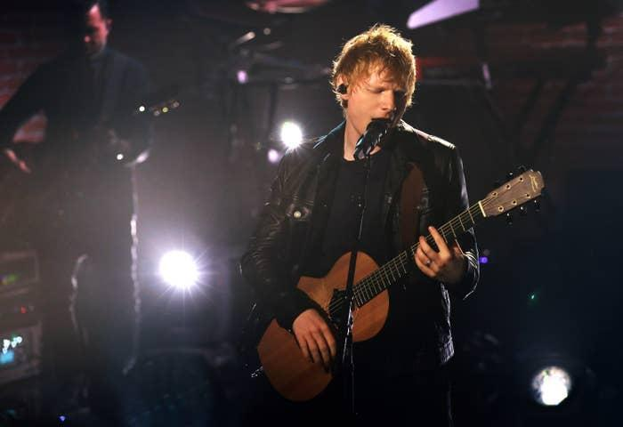 Ed playing his guitar and singing on stage