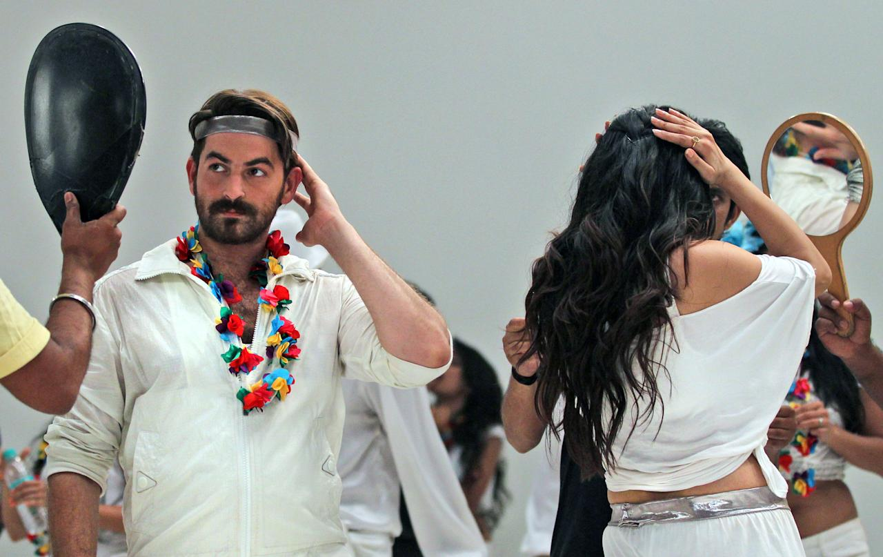 "In this April 21, 2013 photograph, Indian Bollywood actors Neil Nitin Mukesh, left, and Puja Gupta, back to camera check their make up while shooting their upcoming film ""Shortcut Romeo"" in Mumbai, India. Friday, May 3 marks exactly a hundred years after India's first feature film ""Raja Harischandra,"" a silent movie, was screened in 1913. India produced almost 1,500 movies last year and the industry is expected to grow from $2 billion to $3.6 billion in the next five years, according to consultancy KPMG. (AP Photo/Rafiq Maqbool)"