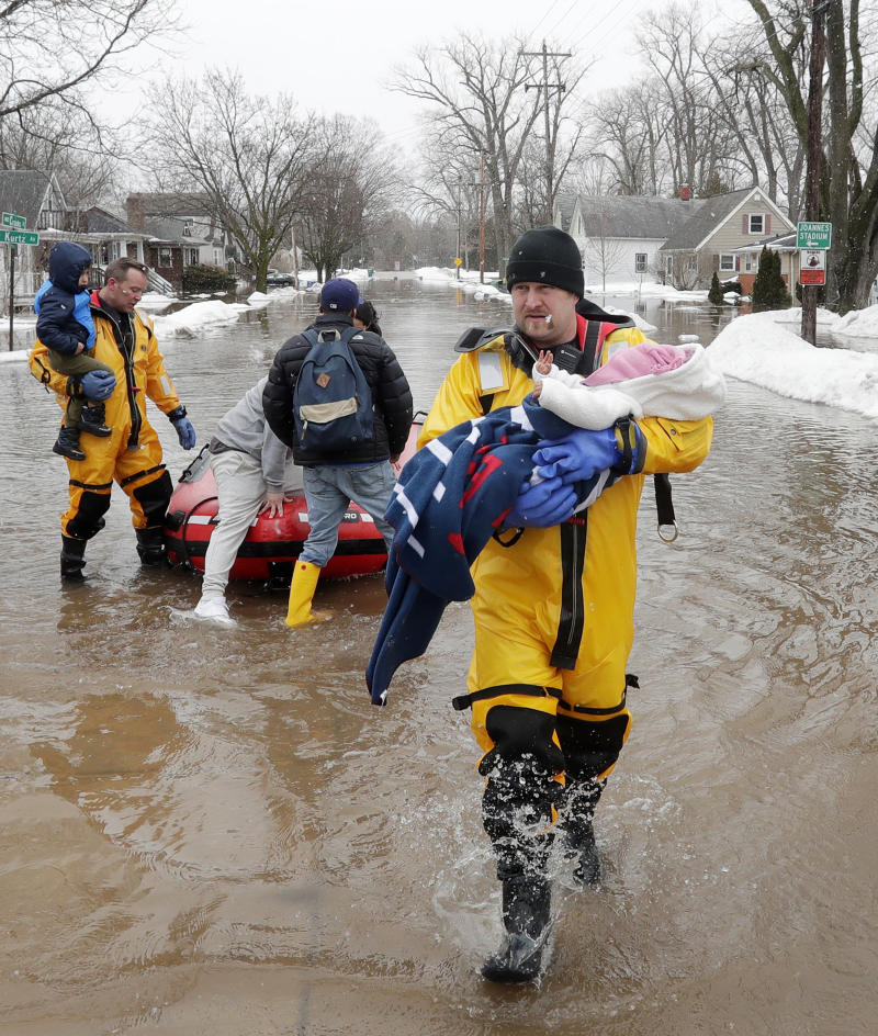 Firefighter Brian Farr carries a baby from the boat as the GBFD assisted residents with home evacuations on Crooks Street due to the East river flooding on March 15, 2019 in Green Bay, Wisconsin.
