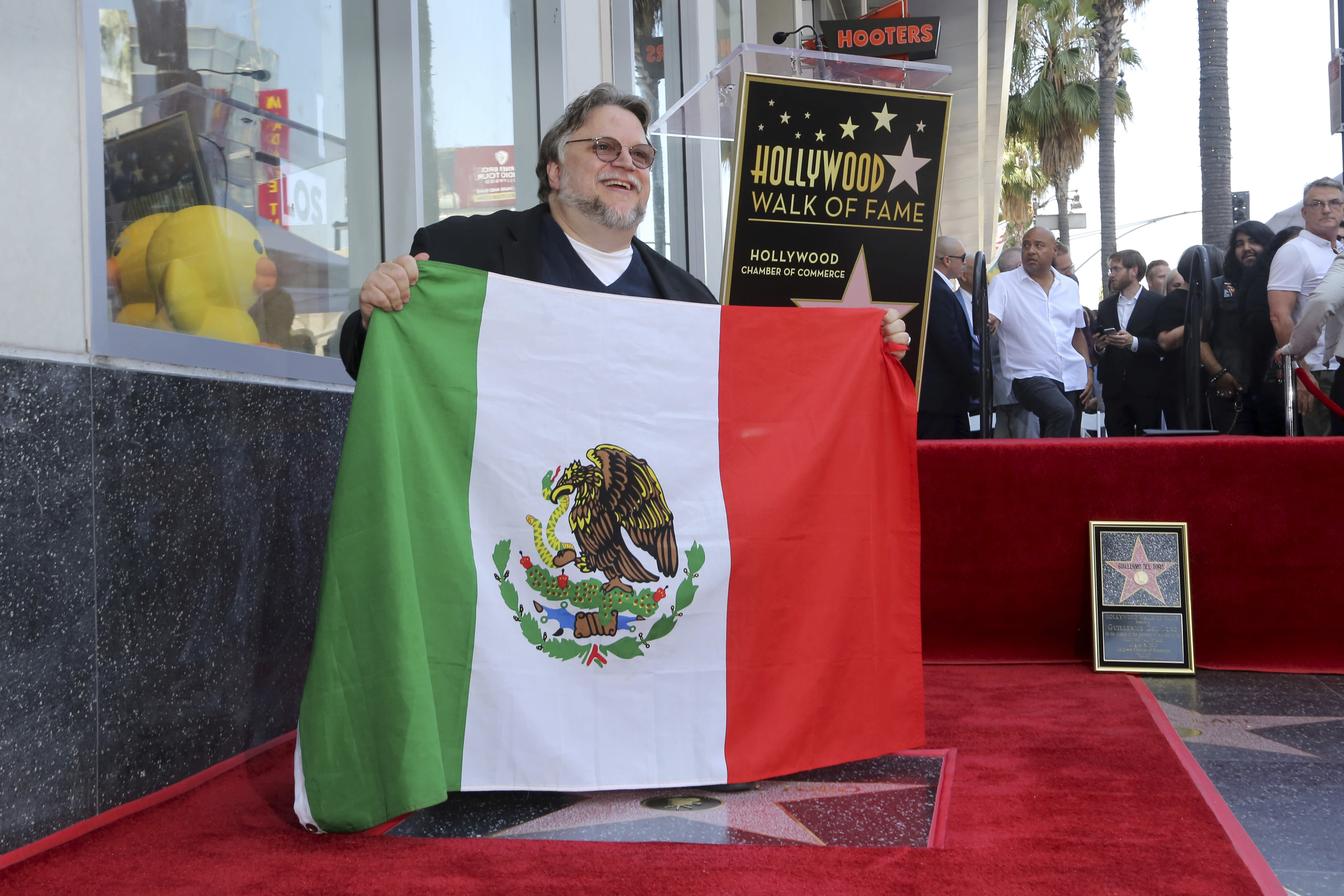 Mexican filmmaker Guillermo del Toro poses with the Mexican flag following a ceremony honoring him with a star at the Hollywood Walk of Fame on Tuesday, Aug. 6, 2019, in Los Angeles. (Photo by Willy Sanjuan/Invision/AP)