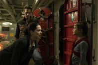 """This image released by Warner Bros. Entertainment shows Alexander Skarsgard, background, Rebecca Hall, foreground left, and Kaylee Hottle in a scene from """"Godzilla vs. Kong."""" (Chuck Zlotnick/Warner Bros. Entertainment via AP)"""