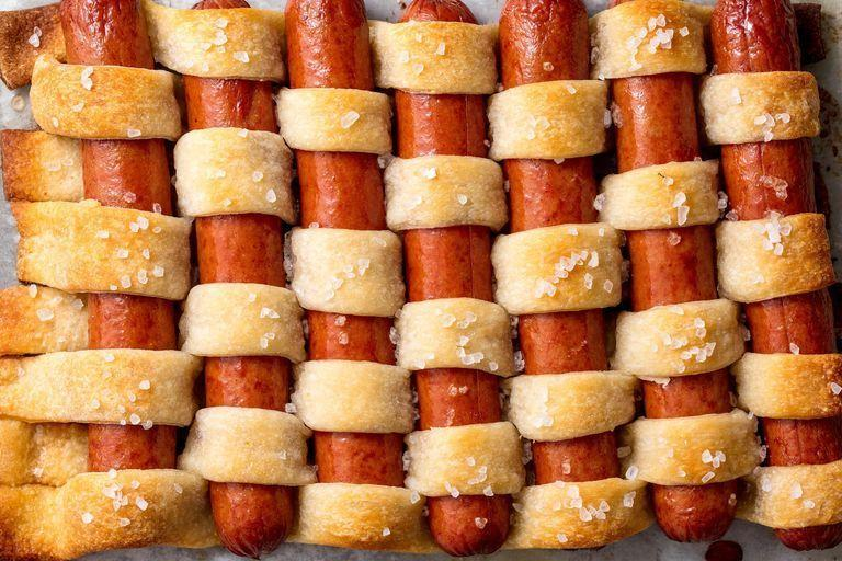 """<p>This app might look complicated but we swear it isn't. Plus its a fun twist on the classic pigs in a blanket that's great for a crowd!</p><p>Get the recipe from <a href=""""https://www.delish.com/cooking/recipe-ideas/recipes/a47591/pigs-in-a-quilt-recipe/"""" rel=""""nofollow noopener"""" target=""""_blank"""" data-ylk=""""slk:Delish"""" class=""""link rapid-noclick-resp"""">Delish</a>.</p>"""