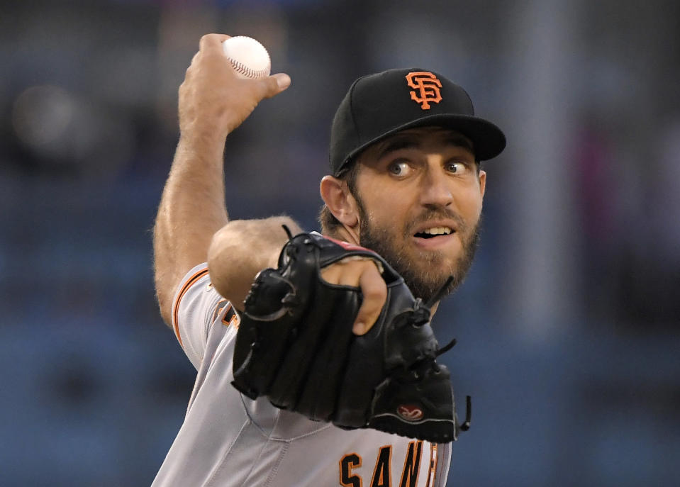 FILE - In this Aug. 13, 2018, file photo, San Francisco Giants starting pitcher Madison Bumgarner throws to the plate during the first inning of a baseball game against the Dodgers in Los Angeles. San Francisco will be younger, with fewer big names, for sure. And some of those big names _ take Buster Posey, Brandon Belt and Madison Bumgarner _ are eager for fresh starts after injury-shortened years in 2018. (AP Photo/Mark J. Terrill, File)