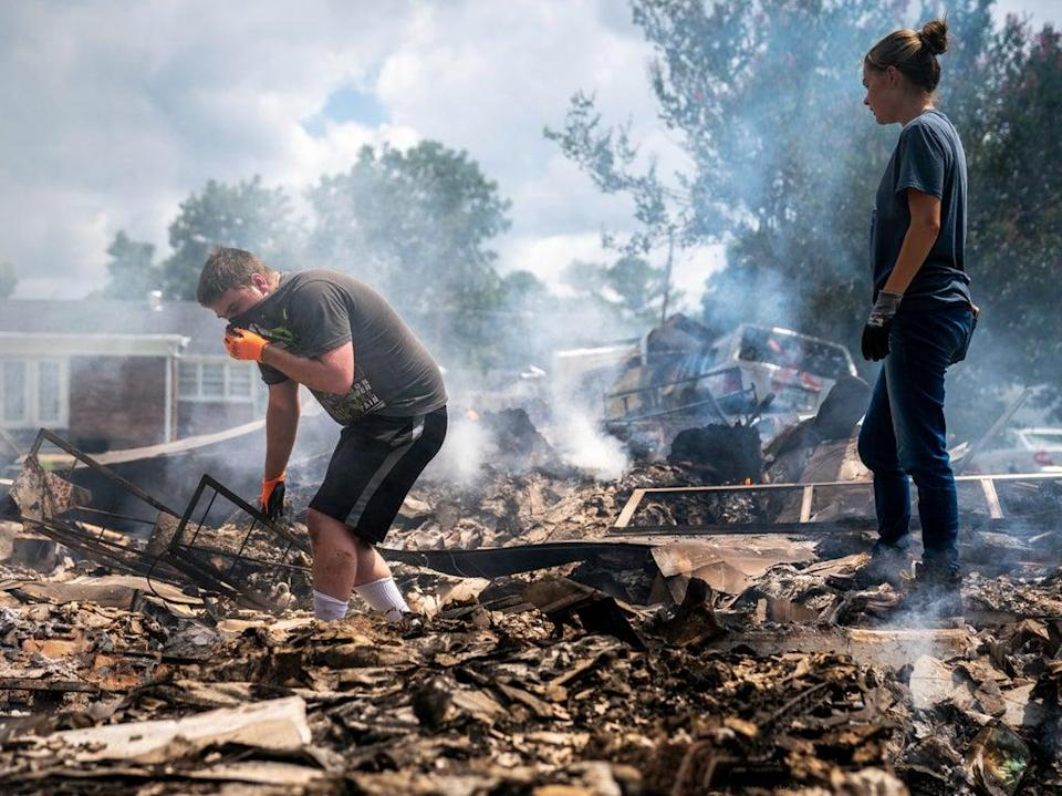 Josh Whitlock and Stacy Mathieson look through what is left of their home after it burned following flooding in Waverly, Tennesse on  Sunday 22 August 2021 (Andrew Nelles/The Tennessean/AP)