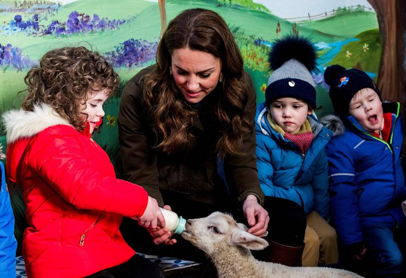 Britain's Catherine, Duchess of Cambridge reacts as she helps children bottle-feed a lamb during her visit to Ark Open Farm near Belfast on February 12, 2020, as part of her tour of the UK to promote her landmark survey on the early years, '5 Big Questions on the Under-Fives'. (Photo by Liam McBurney / POOL / AFP) (Photo by LIAM MCBURNEY/POOL/AFP via Getty Images)