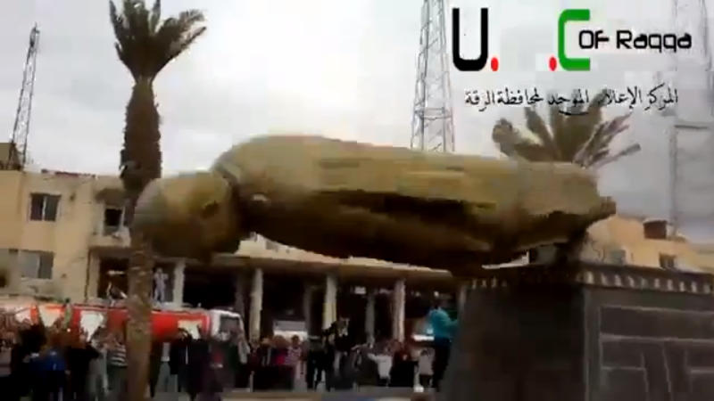 In this Monday, March 4, 2013 image taken from video obtained from Ugarit News, which has been authenticated based on its contents and other AP reporting, a statue of former Syrian President Hafez Assad falls in a central square in Raqqa, Syria. Syrian rebels pushed government troops from most of the northern city of Raqqa Monday, setting off celebrations in a central square where scores of cheering protesters tore down a bronze statue of President Bashar Assad's late father and predecessor, activists said. (AP Photo/Ugarit News via AP video)