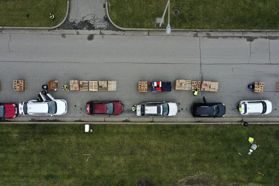Volunteers load boxes of food into a line of waiting cars.