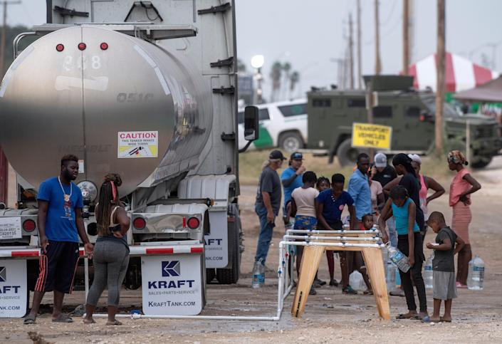 Haitians line up to fill containers with fresh water from a tanker truck beside their camp beneath Del Rio's International Bridge Tuesday Sept. 21, 2021